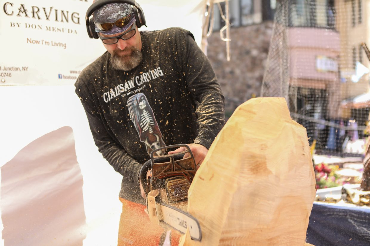 Don Mesuda carves into a chunk of wood with a chainsaw as it begins to take flight as an eagle for Beaver Creek's Hike to the Mic weekend event Friday, Sept. 15, in Beaver Creek. Mesuda used to be in a career in electrical contracting.