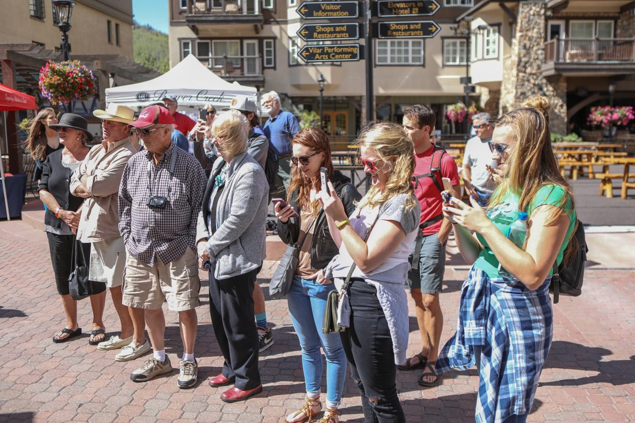 A crowd gathers to watch Don Mesuda carve wood with a chainsaw as it begins to take flight as an eagle for Beaver Creek's Hike to the Mic weekend event Friday, Sept. 15, in Beaver Creek. Mesuda did carving demonstrations all three days of the event.