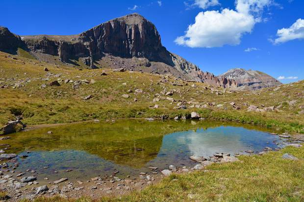 A stunning reflection of an unnamed 13,000 foot mountain in a shallow pool within the Uncompahgre Wilderness area in the San Juan mountain Range.