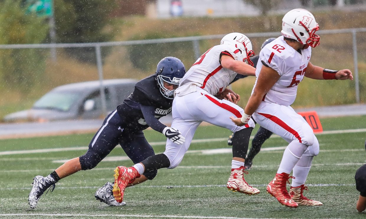 Vail Christian's Roy Valenzuela goes for a tackle against Hotchkiss Saturday, Sept. 23, in Edwards. A cold rain fell throught the entire game.