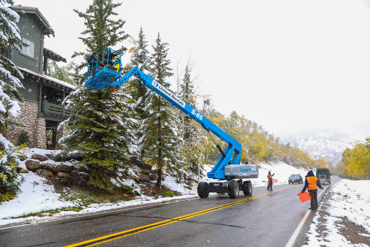 Workers from Alpine Landscape & Construction hang holiday lights in the snow Monday, Oct. 2, in Beaver Creek. The snow makes it feel closer to the holidays than Halloween.