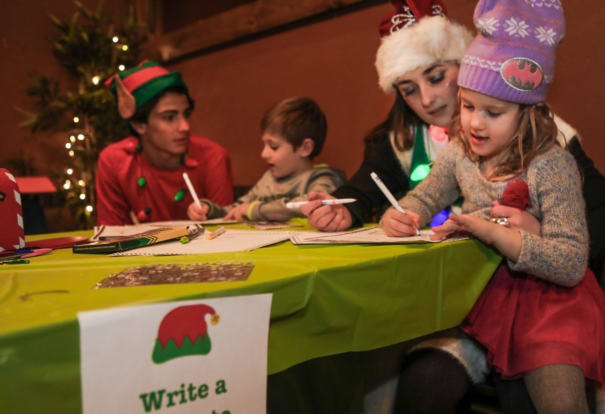From left, Blake Moller and Hannah Kline help Lucas Harrison, 6, and Sophia Harrison, 5, write letters to Santa Clause during the Cocoa and Cocktails event on Wednesday, Dec. 13, at Etown in Edwards. The students were raising money for a CGA Educational Scholarship to take trips to help the needy in Nepal and Nicaragua. The students have to work for the funds instead of relying on donors.