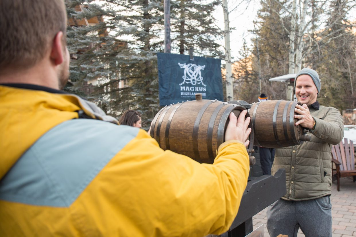Trevor Rappleye (left) and Chad Swift (right) compete against one another in the cask raise at the Highland Park Magnus Whiskey tasing at Vail Snowdays, Friday.