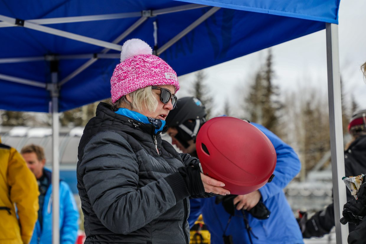 Kim Greene, with Vail Health, adjusts a helmet at the safety tent on Saturday, Jan. 13, in Vail. Greene says she works for the hospital but wants to keep people out of it with basic safety knowledge on the hill.
