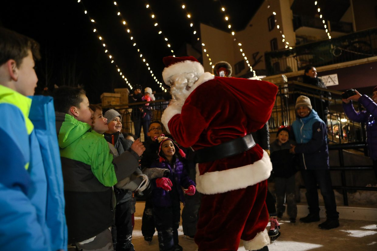 Santa greets kids at the ice rink before heading up the gondola for the Bright Futures holiday party for the Buddy Mentor program on Tuesday, Dec. 19, in Vail. The kids ice skated and opened gifts as part of the annual holiday tradition.