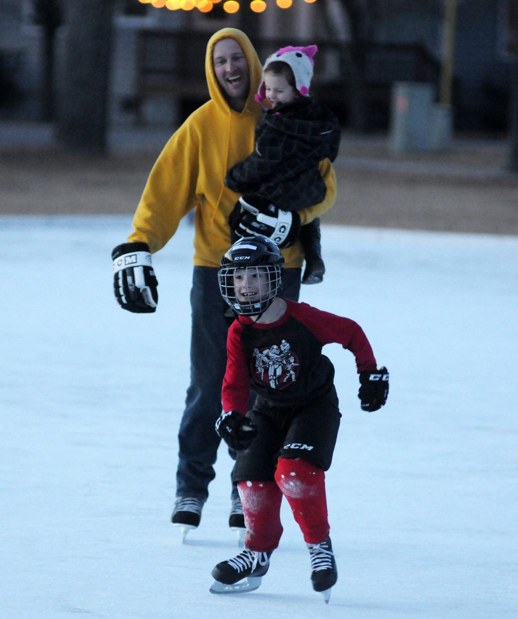 Eagle Ice Rink 1 KA 1-17-18 Kristin Anderson Eagle resident Jim Swanson holds his daughter Piper, 3, while skating with his son Calvin, 8, Wednesday at the Eagle Town Park Ice Rink.