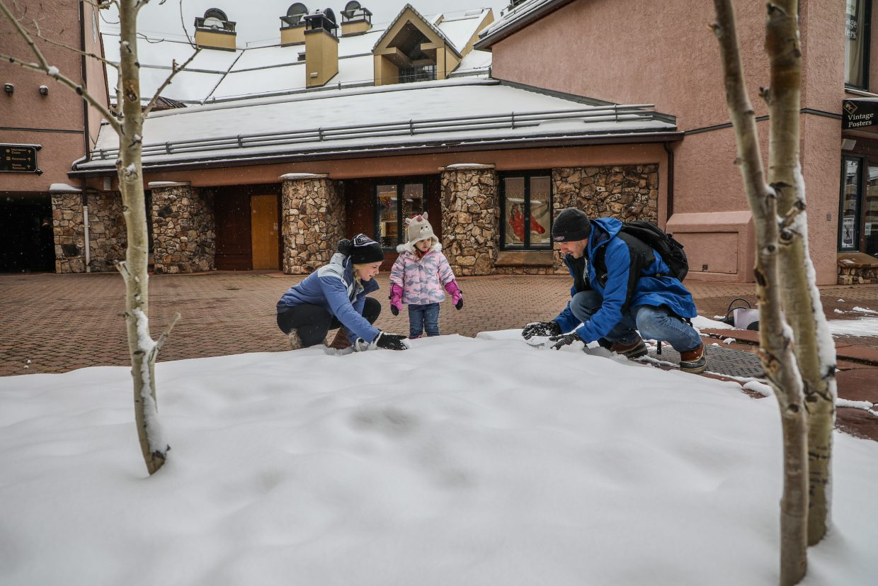 Brent, Lindsay and Landry, 3, of Texas, build a snowman with the freshly-fallen snow on Friday, Jan. 12, in Beaver Creek. Landry just got new gloves to play in the snow.