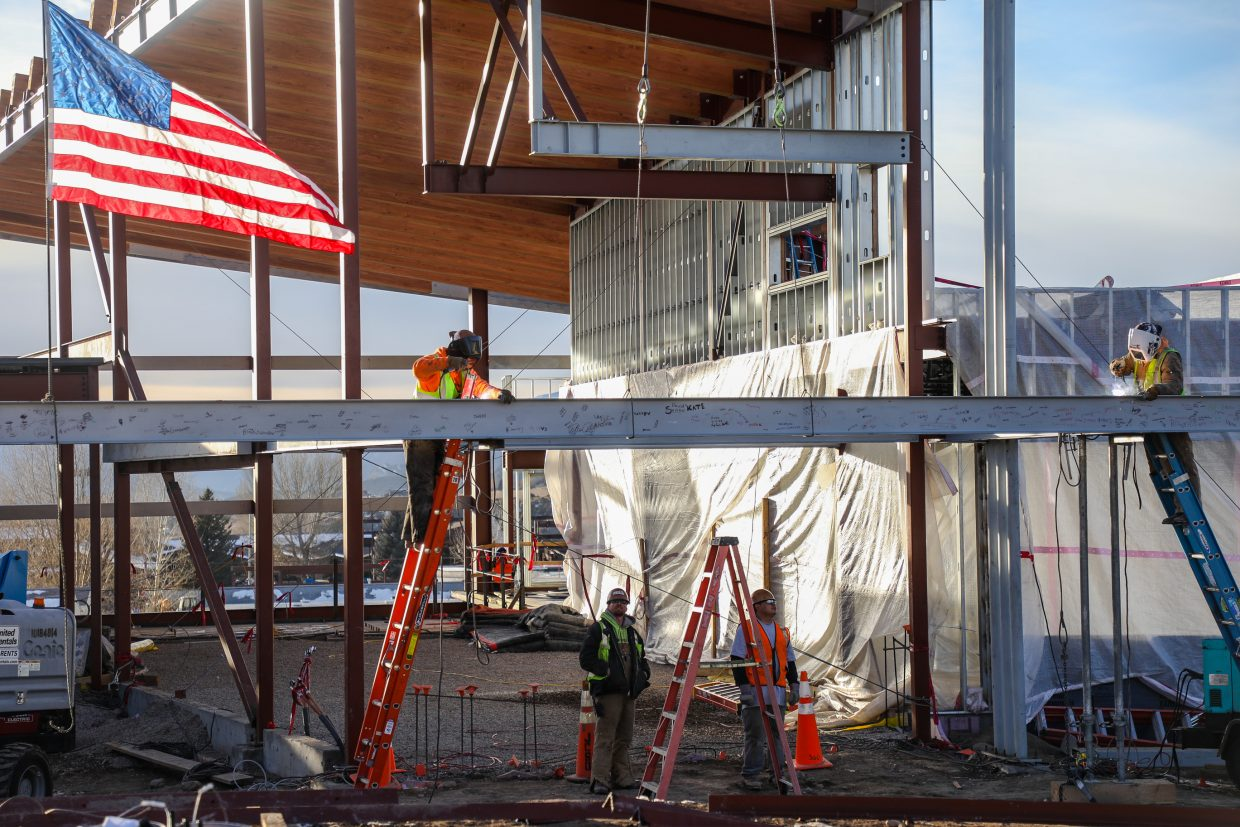 Workers weld the final steel beam into place of the new Eagle Valley Elementary School on Wednesday, Jan. 24, in Eagle. The beam was signed by students and Eagle County School Board members.