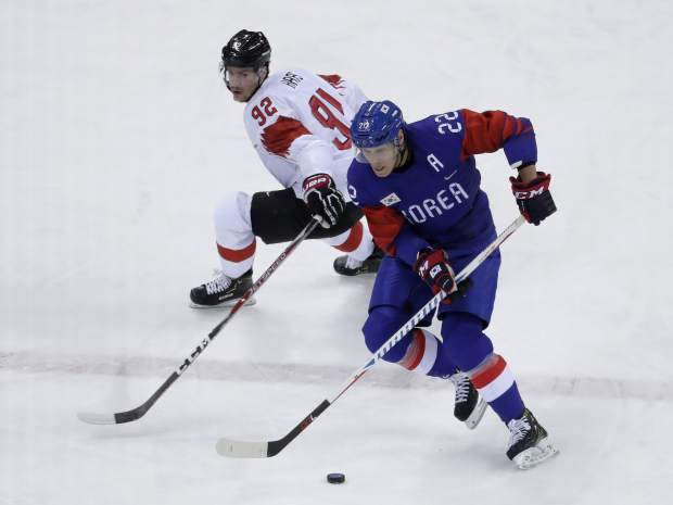Mike Testwuide (22), a Vail native who plays for South Korea, drives the puck against Gaetan Haas (92), of Switzerland, during the first period of the preliminary round of the men's hockey game at the 2018 Winter Olympics in Gangneung, South Korea, Saturday, Feb. 17, 2018. Testwuide marched with both North Korea and South Korea in the opening ceremonies.