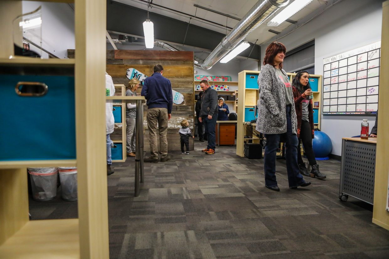 People mingle in the new space of SOS Outreach in the official unveiling of the redesign by Avon-based Select Surfaces on Monday, Feb. 12, in Edwards. New floors, walls and paint were only a few of the renovations done.