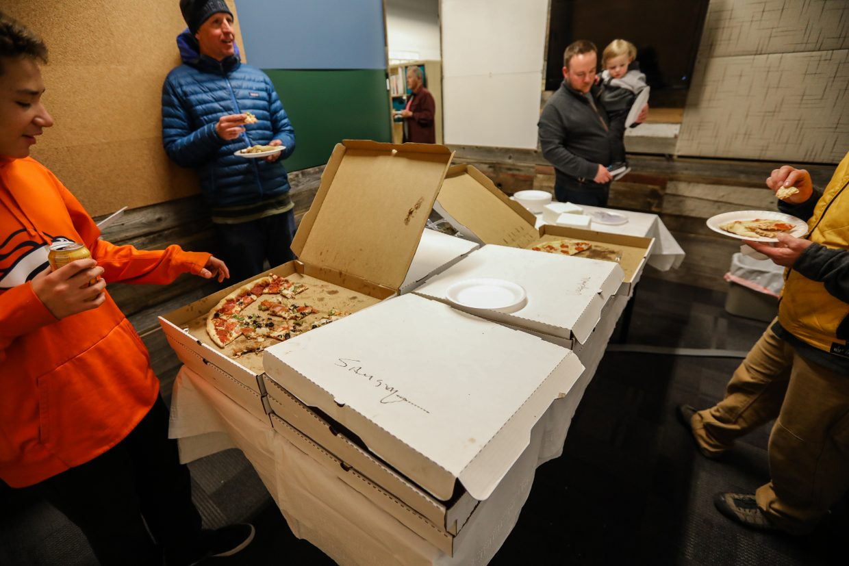 Carlos Armenta-Goodwin goes for some pizza in the new conference room in the SOS building on Monday, Feb. 12, in Edwards. Through the Design for a Difference, SOS now has more utilized space, including a new conference room.