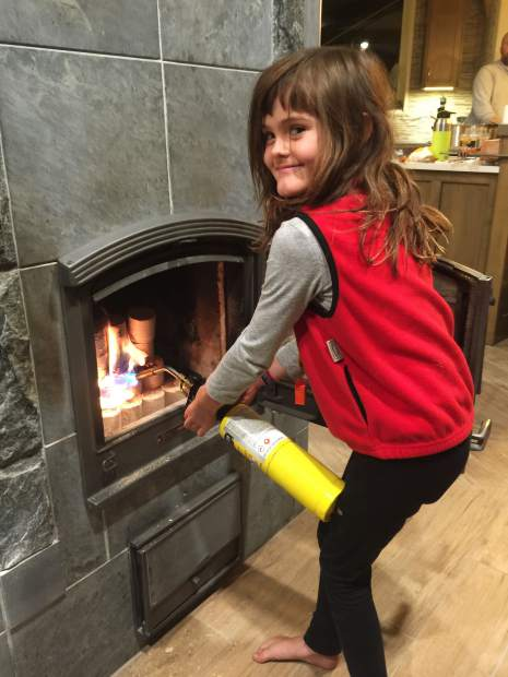 Kate Sheldon's daughter Reeve fires up the soapstone Finnish fireplace that doubles as a high-efficiency, clean-combustion heating system.