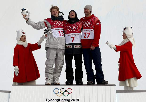 Gold medal winner Sebastien Toutant, of Canada, is flanked by silver medal winner Kyle Mack, of the United States, left, and bronze medal winner Billy Morgan, of Great Britain, during the venue ceremony for the men's Big Air snowboard competition at the 2018 Winter Olympics in Pyeongchang, South Korea, Saturday, Feb. 24, 2018.