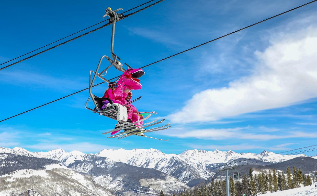 Sean Masler of Edwards rides the Pride Express lift in a pink dinosaur costume for Pink Vail on Saturday, March 24, in Vail.