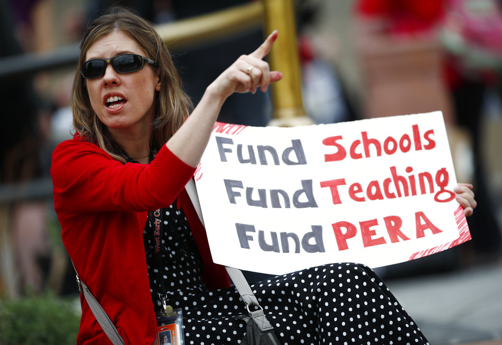 Kristen Rose, a 7th grade English teacher at West Early College in Denver, takes part in a rally outside the State Capitol Monday, April 16, 2018, in Denver. Teachers from around the state were on hand to demand better salaries as lawmakers under the dome were set to debate a pension reform measure to cut retirement benefits as well as take-home pay. (AP Photo/David Zalubowski)