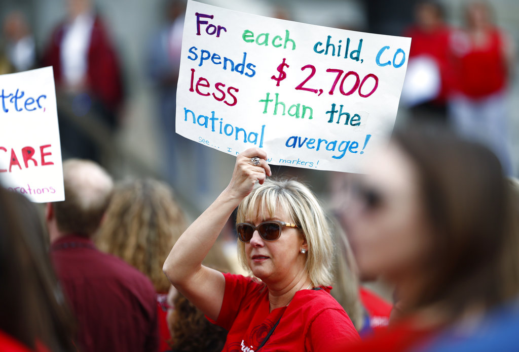An unidentified teacher holds up a placard during a rally outside the State Capitol, Monday, April 16, 2018, in Denver. Teachers from around the state were on hand to demand better salaries as lawmakers under the dome were set to debate a pension reform measure to cut retirement benefits as well as take-home pay. (AP Photo/David Zalubowski)