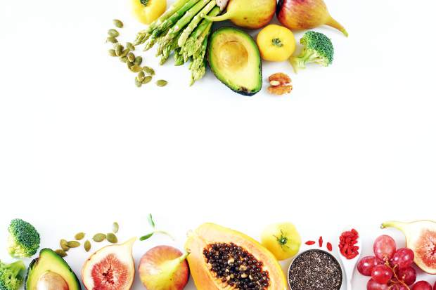 Detox or clean-eating concept with avocado, papaya, grape, broccoli, figs, nuts, seeds, superfoods.