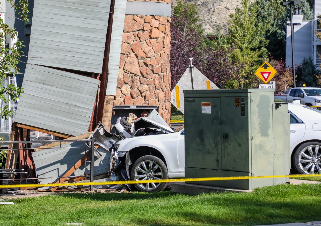 A car is seen crashed into a support beam on the