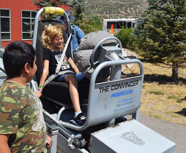 Madisyn Vuorenmaa, 9, rides the Seatbelt Convincer, one of the stations at Camp 911. Kids are strapped in and rolled down a ramp at 3 mph. They hit bottom and an airbag pops open. Camp 911 is in its 27th year, and is hosted twice each summer, once each in Gypsum and Edwards.