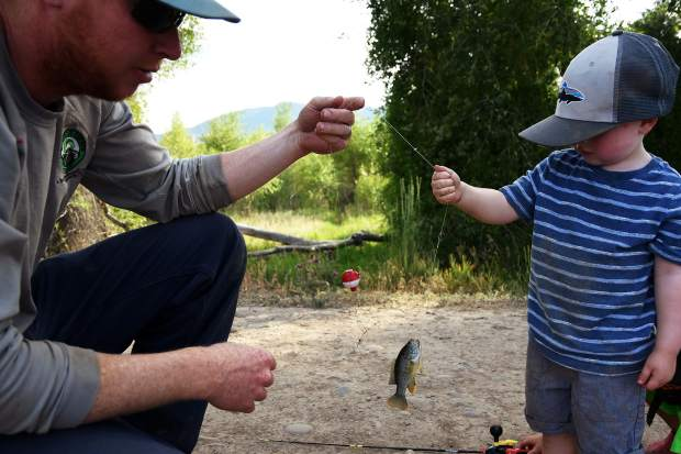 Chris Pitman, left, shows a Blue Gill fish to his son Cason, 2, during the Gypsum Daze Fishing is Fun event on Thursday at Gypsum Ponds.