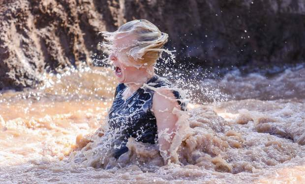 Melinda Brandt emerges from her muddy bath after plunging from a tube during the Mud Run on Saturday, July 14, in Gypsum. The course was at Gypsum Middle School.