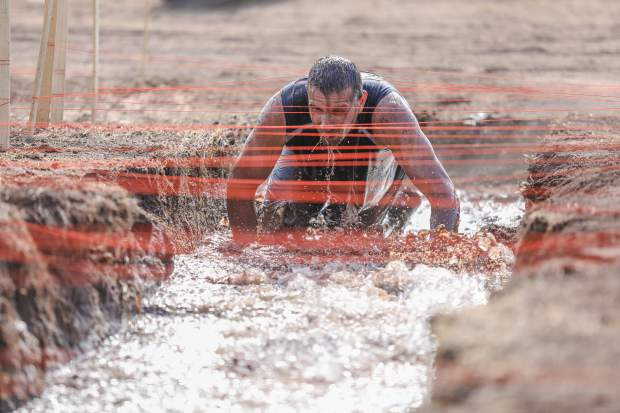 Sheldon Kuhns makes his way through a mud bath, which also has ice in it, during the annual Mud Run Saturday, July 14, in Gypsum. Obstacles varied in the nearly one-mile course.