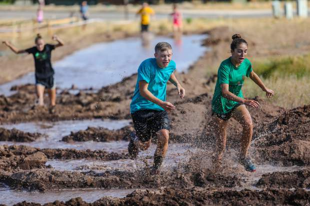 Charlie Callis and Samantha Blair run through, well, mud during the 5th annual Mud Run as part of the Gypsum Race Series on Saturday, July 14, at Gypsum Middle School in Gypsum. Participants who completed the most laps won prices at the Gypsum Recreation Center.