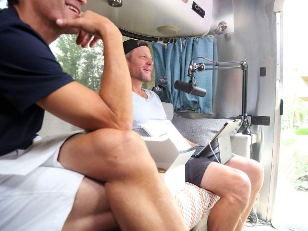 Lance Armstrong, right, sits with George Hincapie as they watch the end of the July 20 stage of the Tour de France before live recording their podcast in Aspen.
