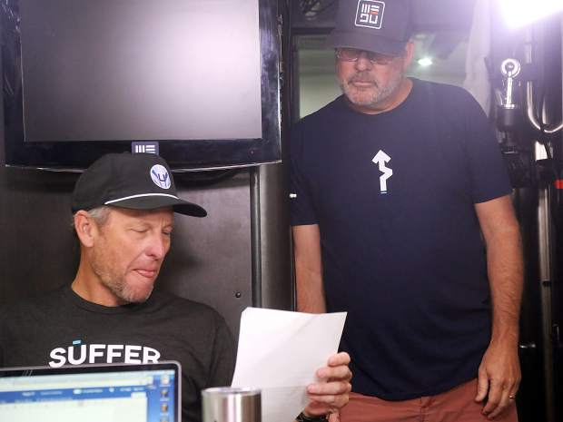 Lance Armstrong, left, talks with co-host JB Hager before live recording their Tour de France podcast