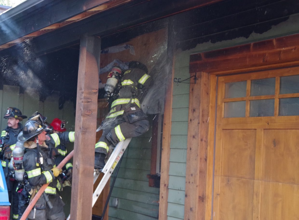 Firefighters with the Eagle River Fire Protection District douse a smoldering hot spot on a home in Minturn. Flames were originally reported up and around the garage of the home on the south end of Main Street in Minturn.