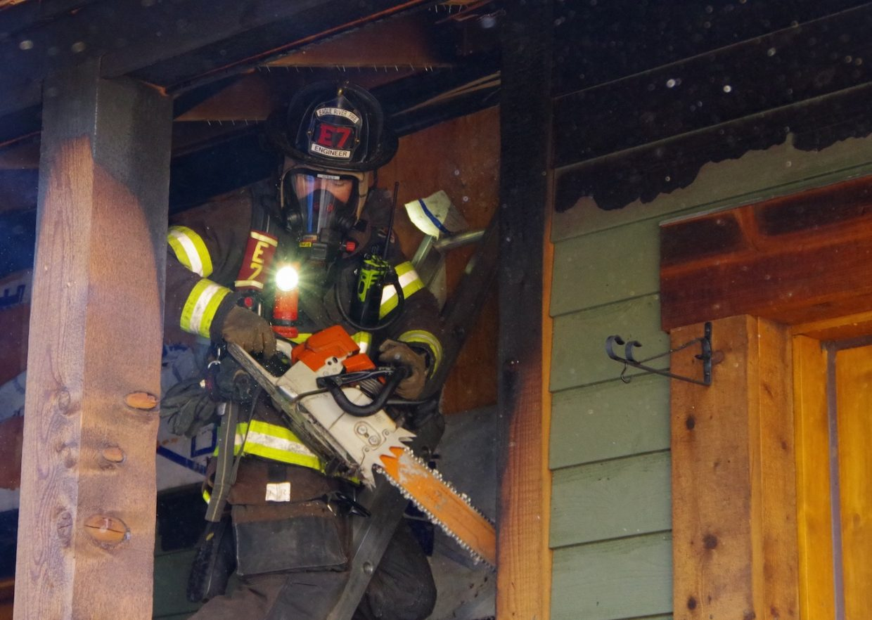 Firefighters with the Eagle River Fire Protection District use a chainsaw to remove siding from a home where a structure fire was reported Tuesday morning, July 3.