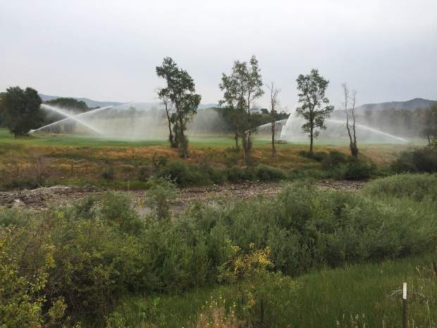 Sprinklers irrigate land on the east side of the Crystal River (in foreground), which is facing one of its driest years in recent history. Low flows on the Crystal have spurred action from the state, including curtailment and a call for instream flows.