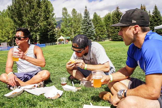 Local friends, Phac Tran (left), Josh Tanner (center) and Bret Burton (right), enjoy barbecue food and music at the Pitmaster BBQ & Music Festival in Avon on Sunday afternoon. Photo By- Rachael Zimmerman