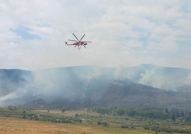 A helicopter working hotspots on the Cabin Lake Fire near Meeker prepares to dip into the South Fork of the White River for water on Thursday.