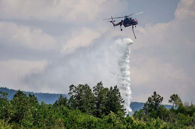 A helicopter makes a water drop near Drop Point 15 on July 27 in El Jebel fighting the Lake Christine Fire.