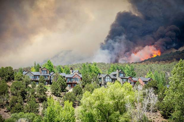Flames rage above homes from the Lake Christine fire in Basalt, Colorado on July 4, 2018.