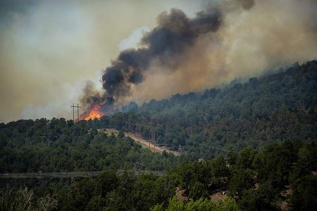 Flames explode near power lines on Basalt Mountain from the Lake Christine fire in Basalt, Colorado on July 4, 2018.