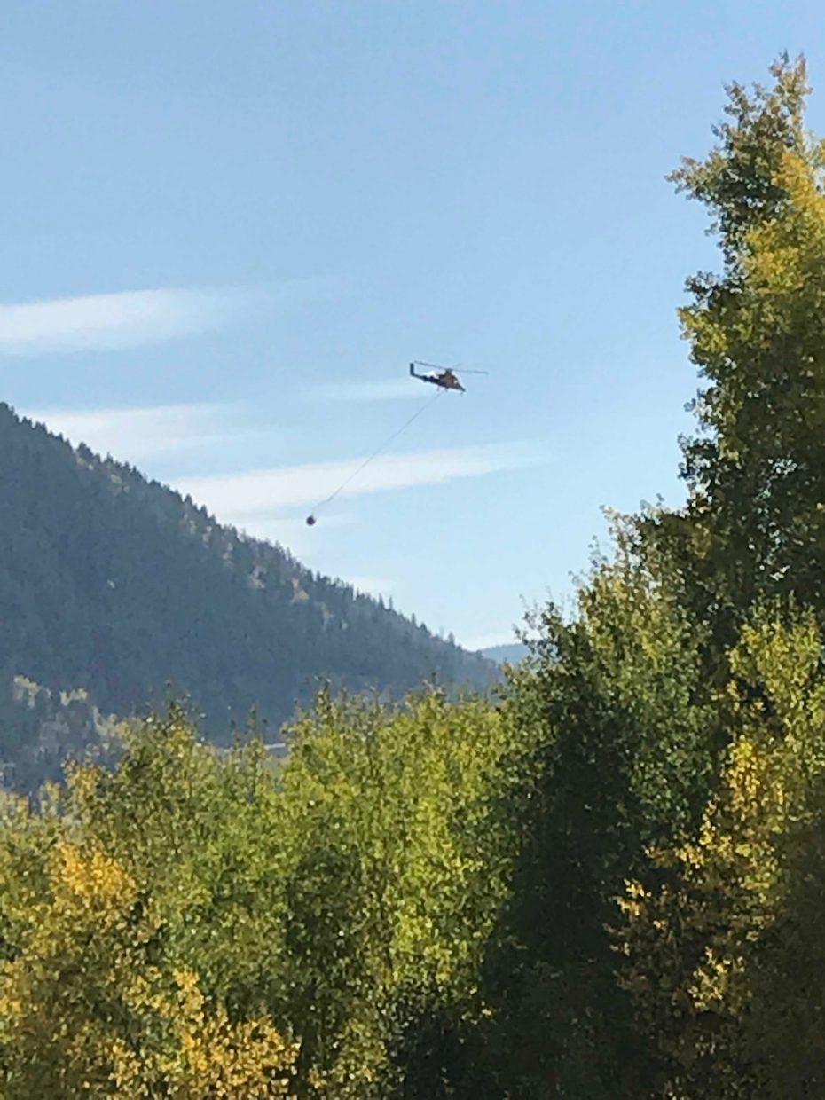 A helicopter dumps water on a wild land fire south of Minturn on Saturday, Sept. 29.