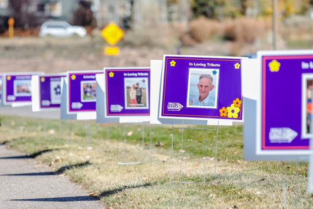 Signs remembering those who fought the battle with Alzheimer's line the beginning of the Walk to End Alzheimer's Saturday, Oct. 20, in Eagle.