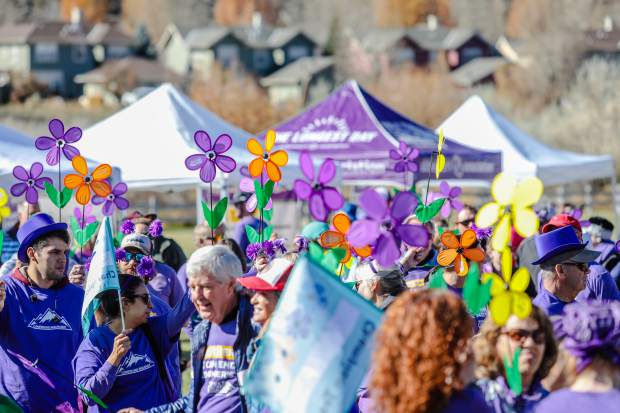 Flowers are held in the air symbolizing the connection those have with Alzheimer's before the Walk to End Alzheimer's Saturday, Oct. 20, in Eagle. The different colors represent the connection with Alzheimer's the person has. Hopes are to add a white flower to represent survivors of Alzheimer's.
