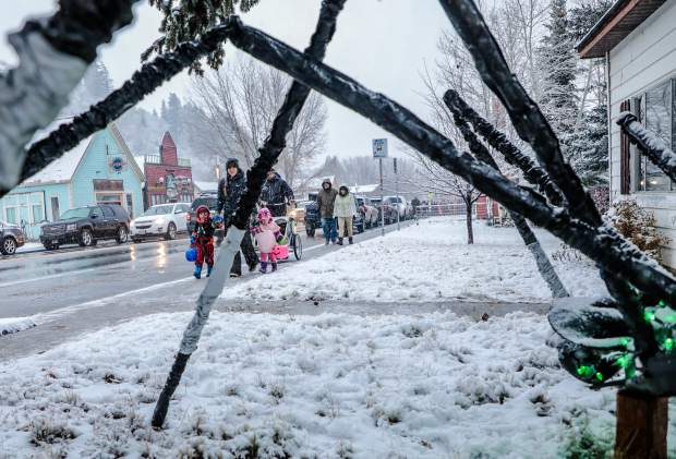 People stroll down Main Street in the snow Trick or Treating Tuesday, Oct. 30, in Minturn. The spider, which is in the foreground, is one of many excellently decorated residences in Minturn.