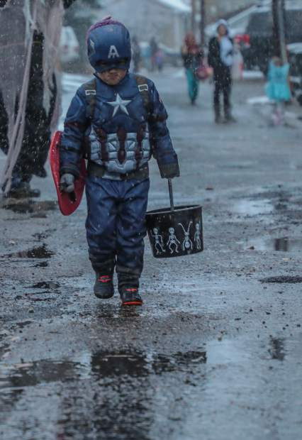 Strait McCullough, 3, also known as Captain America, strolls down the street to the next candy stop at the trick-or-treat event Tuesday, Oct. 30, in Minturn.