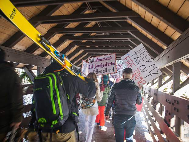 Skiers pass protesters and activists on the Covered Bridge, giving out high-fives or joining in chants in support of the annual Women's March, which took place around the world on Saturday.