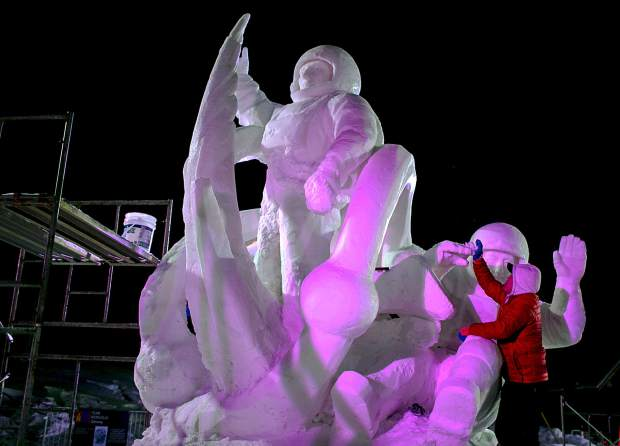 Tserendash Batmunkh, of Mongolia, does final touches of the Discovery masterpiece during the International Snow Sculpture Championships Thursday night, Jan. 24, at the RIverwalk Center in Breckenridge.