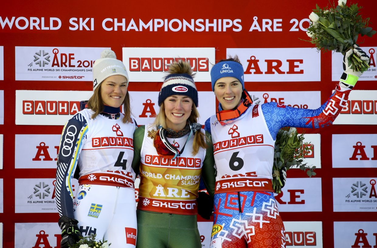 Mikaela Shiffrin shares the podium with Sweden's Anna Swenn Larson, left, and Slovakia's Petra Vlhova, right.