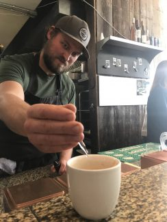 A man squeezes a few drops of a clear liquid into a latte