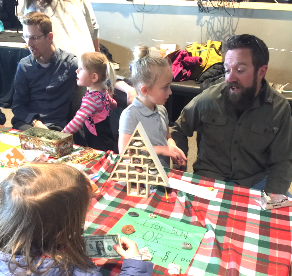 Kindergarten and first grader Dads help their daughters make change, selling scripture rocks and wood crafts: