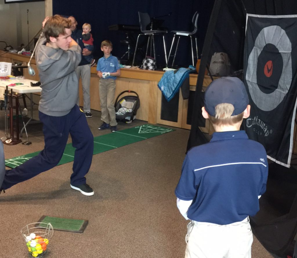 A high school students takes his swings at the indoor golf driving range.