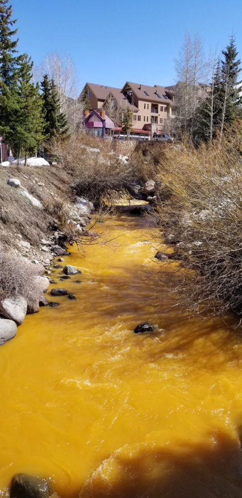 The Blue River turns orange in Breckenridge on Saturday, April 27.
