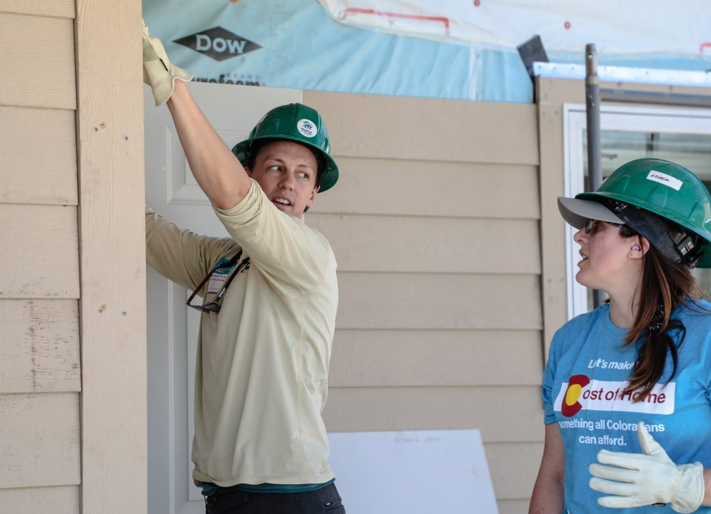 Local state Rep. Dylan Roberts and Liz Peetz, vice president of government affairs for the Colorado Association of Realtors, which sponsors the build day for Habitat for Humanity, install siding at Stratton Flats Thursday in Gypsum.